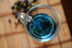 Blauer thailändischer Tee anchan in der Glasschale auf Bambusmatte auf Holztisch, Draufsicht Seifenerz von Blumen des Clitoria na Lizenzfreies Stockbild