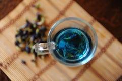 Blauer thailändischer Tee anchan in der Glasschale auf Bambusmatte auf Holztisch, Draufsicht Seifenerz von Blumen des Clitoria na Lizenzfreies Stockfoto