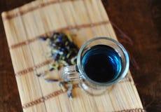 Blauer thailändischer Tee anchan in der Glasschale auf Bambusmatte auf Holztisch, Draufsicht Seifenerz von Blumen der Klitoris na Lizenzfreie Stockbilder