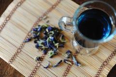 Blauer thailändischer Tee anchan in der Glasschale auf Bambusmatte auf Holztisch, Draufsicht Seifenerz von Blumen der Klitoris na Stockfotografie