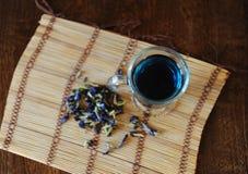 Blauer thailändischer Tee anchan in der Glasschale auf Bambusmatte auf Holztisch, Draufsicht Seifenerz von Blumen der Klitoris na Lizenzfreie Stockfotografie