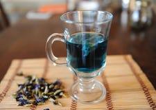 Blauer thailändischer Tee anchan in der Glasschale auf Bambusmatte auf Holztisch Seifenerz von Blumen des Clitoria nahe bei Schal Lizenzfreie Stockfotografie