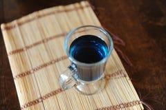 Blauer thailändischer Tee anchan in einer Glasschale auf einer Bambusmatte auf einem Holztisch, Draufsicht Lizenzfreie Stockbilder