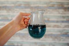 Blauer thailändischer Tee anchan im Glaskrug in einer ausgestreckten Hand auf einem hellen hölzernen gestreiften Hintergrund Lizenzfreies Stockbild