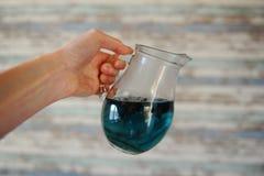 Blauer thailändischer Tee anchan im Glaskrug in einer ausgestreckten Hand auf einem hellen hölzernen gestreiften Hintergrund Lizenzfreie Stockfotografie