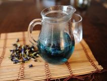 Blauer thailändischer Tee anchan im transparenten Glaskrug auf Bambusmatte auf Holztisch Seifenerz von Trockenblumen des Clitoria Lizenzfreie Stockbilder
