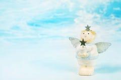 Blauer träumender Weihnachtsschutzengel, der einen Stern in seinem Han hält Lizenzfreie Stockbilder