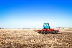 Blauer Traktor auf dem Gebiet Stockfoto