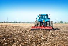 Blauer Traktor auf dem Gebiet Stockfotografie