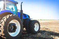 Blauer Traktor auf einem Gebiet Lizenzfreies Stockfoto