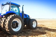 Blauer Traktor auf einem Gebiet Stockfotos