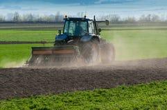 Blauer Traktor ausgerüstet mit der Egge, die an dem Feld arbeitet Lizenzfreies Stockfoto