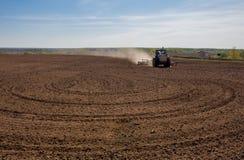 Blauer Traktor, der ein Feld bevor dem Pflanzen pflügt lizenzfreie stockbilder