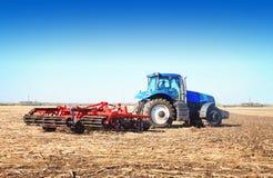 Blauer Traktor, der in einem Gewann arbeitet Stockbild