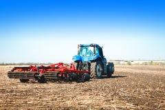Blauer Traktor, der in einem Gewann arbeitet Lizenzfreie Stockbilder
