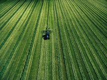 Blauer Traktor, der grünes Feld, Vogelperspektive mäht Stockbilder