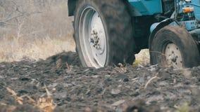 Blauer Traktor mit dem Pflug mit vier Furchen, der Feld mit schwarzem Bodenabschluß herauf Ansicht pflügt stock video footage