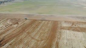 Blauer Traktor mit vier Ploughshares, die trockenes fruchtbares Landbraun kultivieren Das Konzept der Landwirtschaft Das ausgezei stock footage