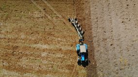 Blauer Traktor mit vier Ploughshares, die trockenes fruchtbares Landbraun kultivieren Das Konzept der Landwirtschaft Das ausgezei stock video footage