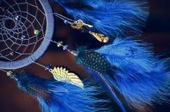 Blauer Traumfänger, der am dunklen Hintergrund hängt Lizenzfreies Stockbild