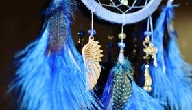 Blauer Traumfänger, der oben am dunklen Hintergrundabschluß mit Suspendierungsflügel hängt Stockbilder