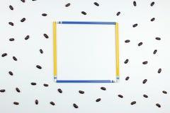 Blauer und gelber Bleistiftrahmen mit roten Bohnen auf weißem Hintergrund Stockfotos