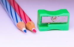 Blauer und roter Bleistift mit Bleistiftspitzer Lizenzfreie Stockbilder