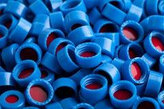 Blauer und roter Plastik bedeckt Hintergrund mit einer Kappe Stockfotografie