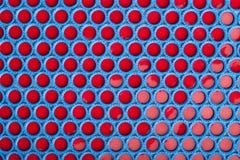 Blauer und roter Plastik bedeckt Hintergrund mit einer Kappe Stockfotos