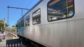 Blauer und silberner Zug kreuzt eine Straße in Melbourne stock video