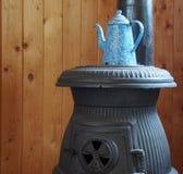 Blauer und weißer gesprenkelter Kaffee-Topf auf Potbellied Ofen Stockfoto