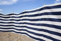 Blauer und weißer gestreifter Windschutz am Strand Stockfotos