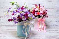 Blauer und weißer lisianthus Eustoma-Blumenblumenstrauß n ein weißer hölzerner Hintergrund Stockfotos