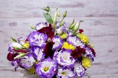 Blauer und weißer lisianthus Eustoma-Blumenblumenstrauß n ein weißer hölzerner Hintergrund Stockfotografie