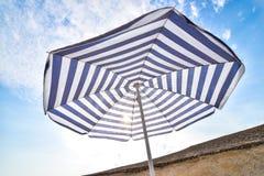Blauer und weißer Sonnenstrandschirm und blauer Himmel mit Wolken Lizenzfreies Stockbild