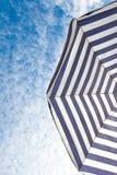 Blauer und weißer Sonnenstrandschirm und blauer Himmel mit Wolken Stockfotos