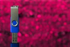 Blauer USB-Blitz-Antrieb auf rosa Hintergrund unscharf Stockfotografie