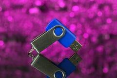 Blauer USB-Flash-Speicher auf rosa Hintergrund unscharf Lizenzfreie Stockbilder