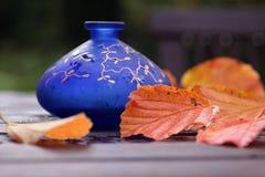 Blauer Vase mit Herbstdekorationen lizenzfreie stockfotos