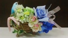 Blauer Vogel auf Blumenkorb Stockbild