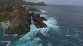 Blauer von der LuftMeereswoge auf sandiger beachBig Welle, die auf Felsenküste zusammenstößt stock video footage
