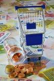 Blauer Warenkorb- und Münzenstapel Stockfotos