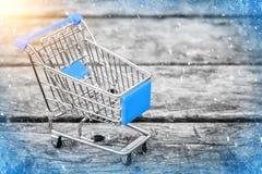 Blauer Warenkorb vom Gemischtwarenladen auf dem alten hölzernen Hintergrund Kaufen des neuen Jahres und des Weihnachten Stockbild