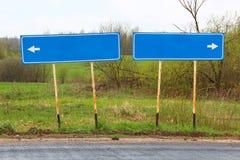 Blauer Wegweiser der leeren Richtung auf der Asphaltstraße auf dem Hintergrund von Grünfeldern und -büschen Lizenzfreies Stockfoto