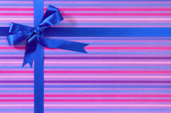 Blauer Weihnachts- oder Geburtstagsgeschenkbandbogen auf Süßigkeitsstreifen-Packpapierhintergrund Lizenzfreie Stockbilder