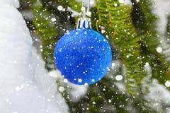 Blauer Weihnachtsball auf dem Tannenzweig bedeckte Schnee Abstraktes Hintergrundmuster der weißen Sterne auf dunkelroter Auslegun Lizenzfreies Stockfoto