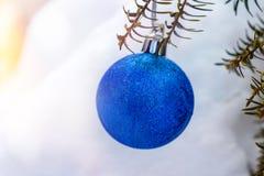 Blauer Weihnachtsball auf dem Tannenzweig bedeckte Schnee Abstraktes Hintergrundmuster der weißen Sterne auf dunkelroter Auslegun Lizenzfreies Stockbild