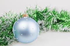 Blauer Weihnachtsball mit grüner Girlande Stockfoto
