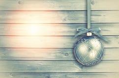 Blauer Weihnachtsflitter mit gelocktem Band auf einem Blau; sonniges hölzernes Stockfotos