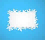 Blauer Weihnachtshintergrund mit Papierschneeflocken. Stockbild